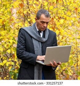 Stylish, handsome man standing  in a park wearing a black suit, white shirt, jeans, scarf, watch and fashionable shoes. Working on his laptop. Surroundings: autumn trees, leaves.
