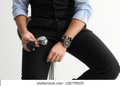 Stylish handsome man with sunglasses and watch on white background, closeup