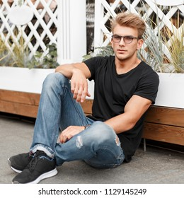 Stylish handsome model with a hairstyle with glasses in a black T-shirt and jeans sitting near a wooden fence on the street