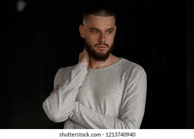 Stylish handsome model man with beard in gray t-shirt on black background