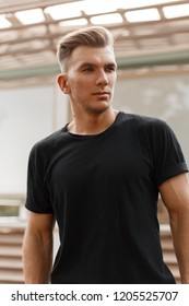 Stylish handsome model man with hairstyle in black t-shirt on the street in the city
