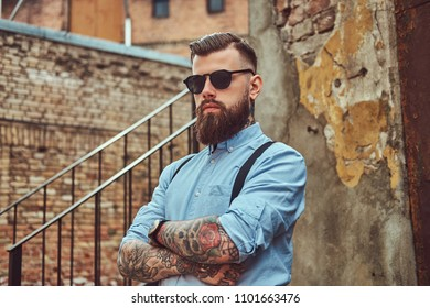 Stylish handsome old-fashioned tattooed hipster guy in a shirt with suspenders, standing near an old building outdoors.
