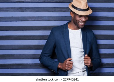 Stylish handsome. Handsome young African man adjusting his jacket and smiling while standing against striped background