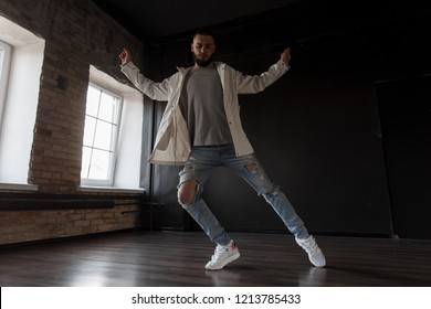 Stylish handsome young attractive man dancer in trendy jacket with fashion ripped jeans and white sneakers dancing in dance studio on dark background. Dance lifestyle
