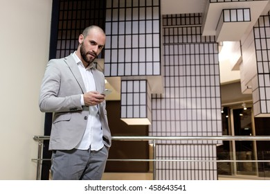stylish handsome young man with with a beard standing indoors on  creative abstract background. Man wearing jacket, shirt in his hand a smartphone. business person browsing internet