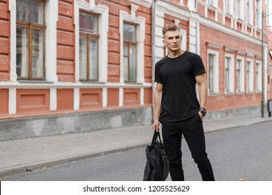 Stylish handsome young man in black fashionable mockup clothes with a black bag walks in the city