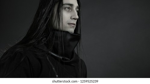 Stylish handsome Young man. Caucasian man's portrait. Sexy man in black clothes with dark long hair. Close-up man's face on a dark background. Gothick style. monochrome