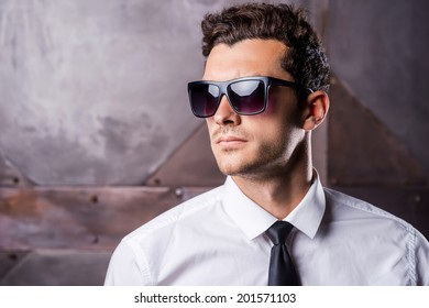 Stylish handsome. Handsome young man in formalwear and sunglasses looking away while standing against metal background