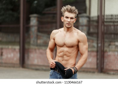 Stylish handsome young man with hairdo with beautiful fitness body with muscles on the street