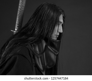 Stylish handsome Young man with Japanese katana sword. Caucasian man's portrait. Sexy man in black clothes with dark long hair. Close-up man's face on a dark background. Ninja.