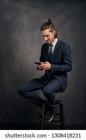 Stylish handsome young man with long hair in a bun, wearing business suit, sitting on bar stool and looking at smartphone in his hands, texting.