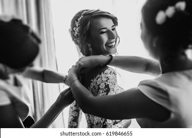 stylish happy bride dressing in dress, smiling to bridesmaids, at window, rustic wedding morning preparation. bridal getting ready. emotional moment. space for text. black white photo