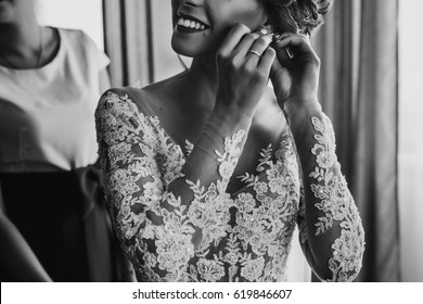 stylish happy bride putting on earrings and smiling, rustic wedding morning preparation in home. bridal getting ready. emotional moment. space for text. black white photo