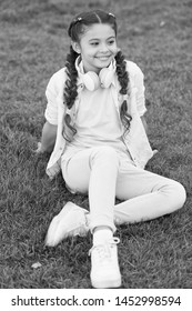 Stylish happy child relax on green grass. little girl listen music. Spring mood. Mp3 player. happy little girl. Audio book. happy kid in headphones. happy childhood. little girl having fun. pure joy.