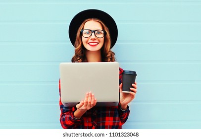 Stylish happy holding laptop computer with coffee cup resting outdoors in city, wearing black hat and red checkered shirt