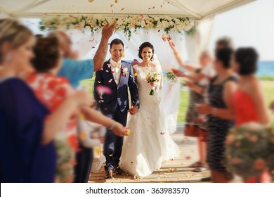 Stylish happy smiling newlyweds on the luxury outdoor wedding ceremony in haze tent near the ocean