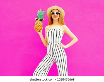 Stylish happy smiling woman holding pineapple wearing striped jumpsuit, summer round straw hat on colorful pink background