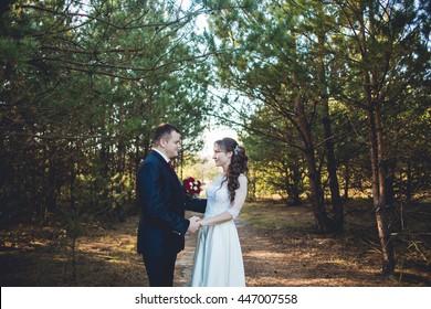 Stylish happy wedding couple on the background beautiful park