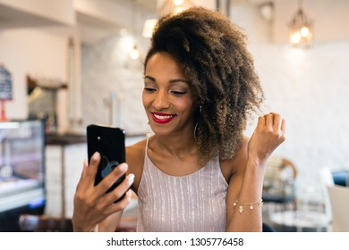 Stylish happy woman showing afro hairstyle taking a selfie photo with smartphone in a cafe bar .