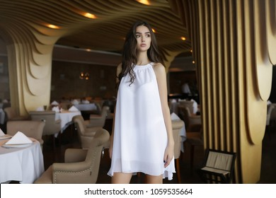 Stylish happy young woman wearing spring outfit,spring heels, bright marine style dress.Posing at cafe and waiting her coffee to go. portrait of smiling girl,emotional teenage girl, bag,dark hair