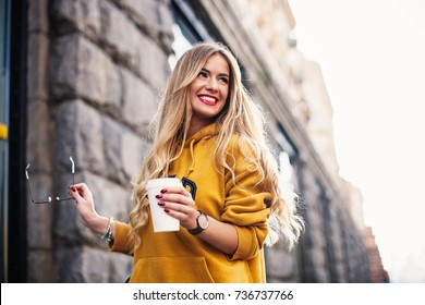 Stylish happy young woman wearing boyfriend jeans, white sneakers bright yellow sweatshirt.She holds coffee to go. portrait of smiling girl in sunglasses Street fashion concept