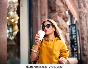 Stylish happy young woman wearing boyfrend jeans, white sneakers bright yellow sweatshirt.She holds coffee to go. portrait of smiling girl in sunglasses she greets friends.
