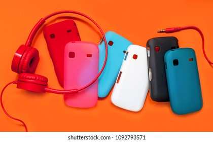 stylish headphones and cases for your phone on an orange background