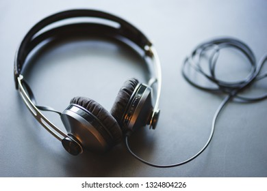 Stylish headphones table top view. Soft focus and beautiful bokeh. Small depth of field. Metal and style design.