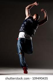 stylish hip-hop man dancing over dark background