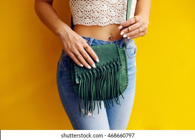 Stylish hippie girl with green vintage suede fringe handbag . Fashion outfit and fashion concept