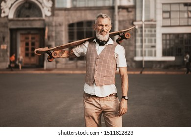 Stylish hipster bearded man with skateboard. Adult model in casual clothes ride longboard on city street. Street lifestyle sport photo