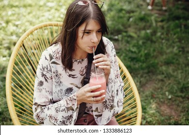 Stylish hipster boho girl drinking strawberry smoothie in glass jar with metal reusable straw at street food festival. Happy woman in sunglasses with healthy drink. Zero waste
