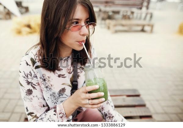 Elegante hipster, chica de edad que bebe espinacas en un frasco de vidrio con paja reutilizable en el festival de comida callejera. Mujer feliz con gafas de sol con bebida saludable en la calle de verano. Desechos cero