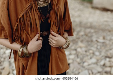 stylish hipster boho traveler woman look. gypsy girl in fringe jacket with feather bronze accessory. wanderlust summer travel. atmospheric moment. space for text.