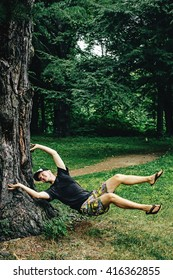 stylish hipster boy levitating and having fun at tree in woods in summer