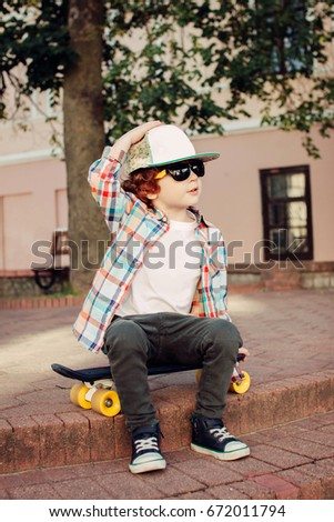 71a961393259 Stylish hipster boy outdoors with a skateboard with glasses and a cap