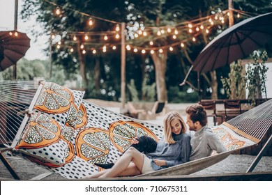 stylish hipster couple cuddling and relaxing in hammock under retro lights in evening summer park. rustic man and woman embracing and resting in forest. space for text. summer vacation