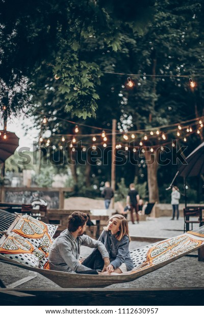 stylish hipster couple family cuddling and relaxing in hammock under retro lights in evening summer park. rustic man and woman embracing and resting in forest. space for text. summer vacation
