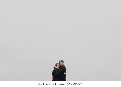 stylish hipster couple hugging gently on background of sky air. sensual atmospheric moment with space for text. fashionable man and woman showing true feelings