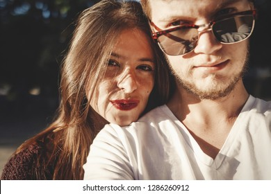 Stylish hipster couple making selfie and embracing in sunlight. Happy family couple in love making self portrait and smiling in evening summer city. Vacation  and travel together