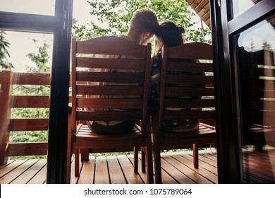 stylish hipster couple relaxing on porch, sitting in wooden cottage and looking at woods in mountains. happy family resting and embracing. summer vacation. atmospheric moment