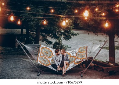 stylish hipster family couple cuddling and relaxing in hammock under retro lights in evening summer park. rustic man and woman embracing and resting in forest. space for text. atmospheric moment