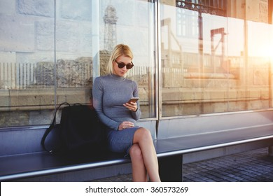 Stylish hipster girl chatting in network via smart phone with her friends while sitting on bus stop in summer day,fashionable woman tourist searching information about bus traffic using cell telephone
