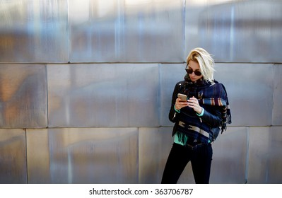 Stylish hipster girl chatting on cell telephone while standing against urban metallic background with copy space area for your text message or advertising content,young female using mobile smart phone