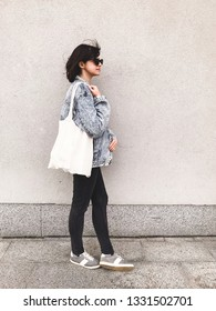 Stylish hipster girl in denim outfit and tote bag posing in city street on background of wall. Phone photo. Fashionable woman with linen bag, sa no to plastic bags. Zero waste