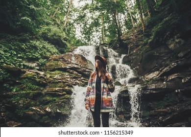 stylish hipster girl in hat with backpack standing at waterfall in forest in mountains. traveler woman exploring woods. travel and wanderlust concept. atmospheric moment