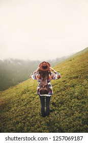 Stylish hipster girl in hat walking on top of mountains. Happy young woman with backpack exploring misty mountains. Travel and wanderlust concept. Amazing atmospheric moment