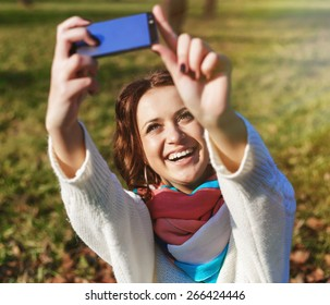 Stylish hipster girl make selfie portrait outdoor in the park