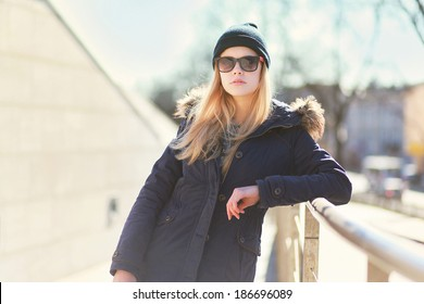 Stylish hipster girl posing in the city a warm day, bright sunshine, fashion photo