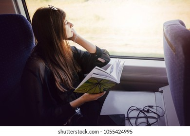 stylish hipster girl reading book at window light in train. travelling by train concept. beautiful young woman holding paper book. travel and transportation. space for text